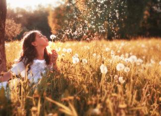 Mädchen mit Pusteblumen auf einer Wiese