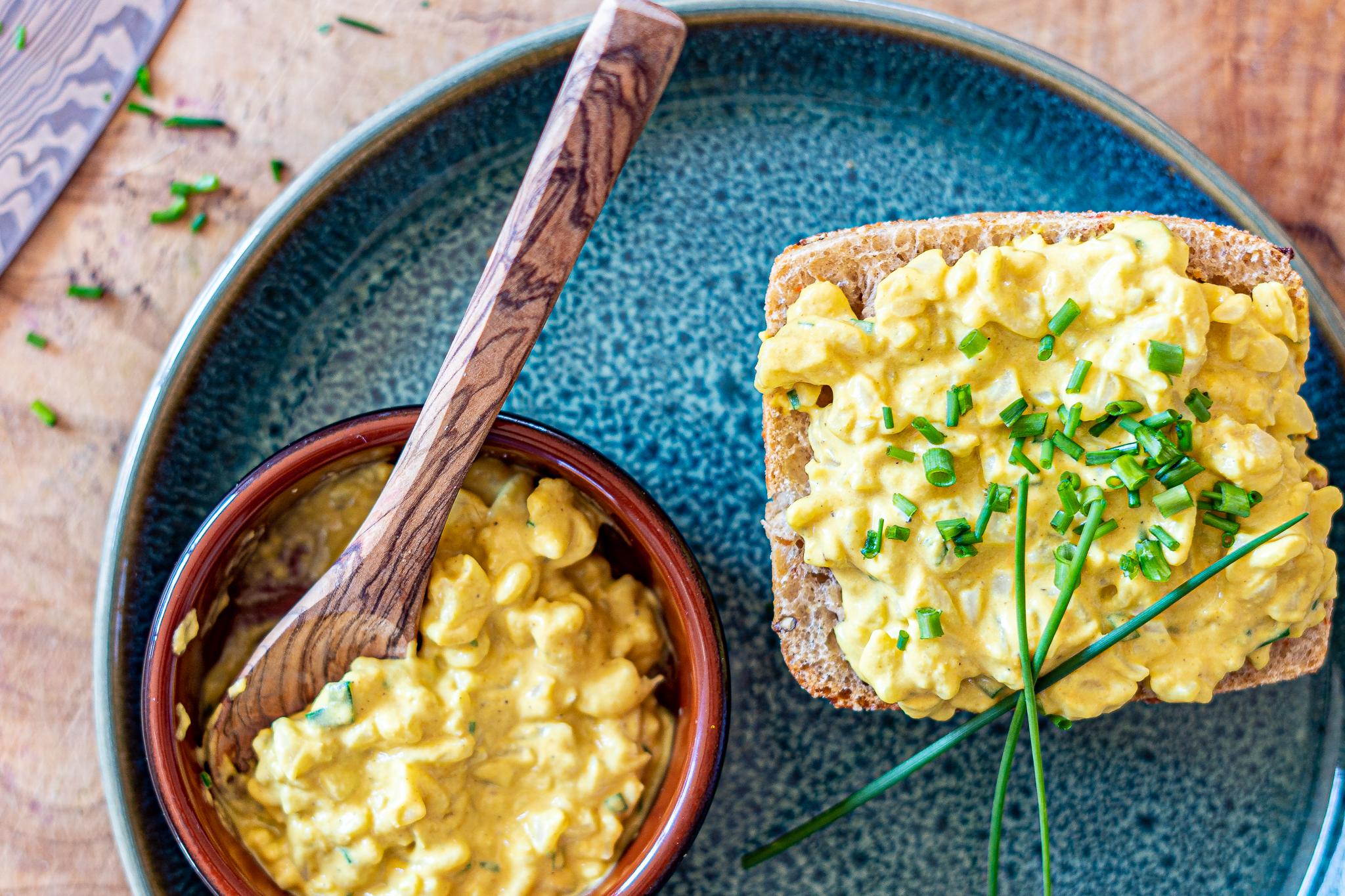 veganer Eiersalat auf einem Brötchen und daneben eine Schüssel